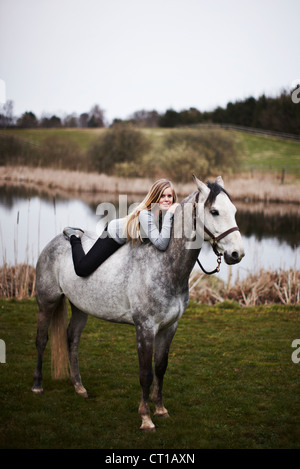 Girl laying on horse in field Banque D'Images