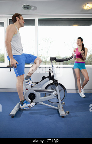 Homme pédaler stationery bicycle in gym Banque D'Images