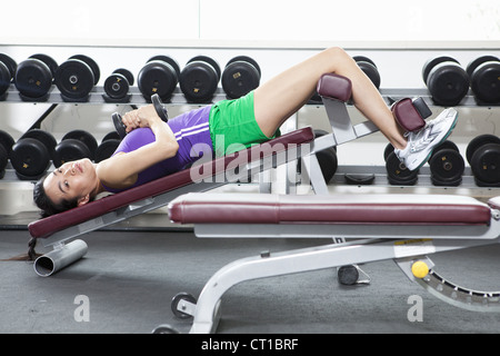 Woman lifting weights in gym Banque D'Images