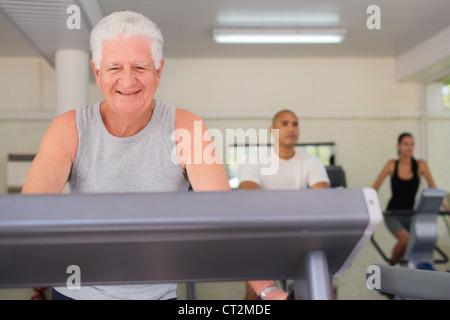 Les gens et les sports, les personnes âgées homme travaillant sur le tapis roulant dans la salle de sport fitness Banque D'Images