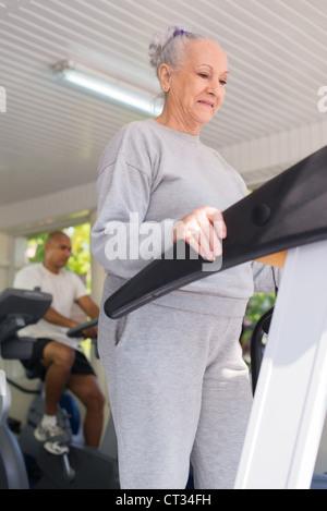 Les gens et les sports, les personnes âgées woman working out sur tapis roulant dans une salle de sport Fitness Banque D'Images