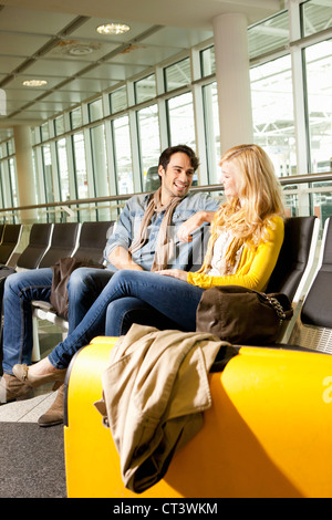 Couple talking in airport waiting area Banque D'Images