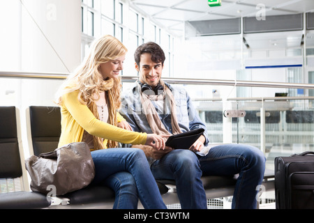 Couple using tablet computer in airport Banque D'Images