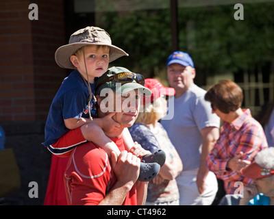 Homme portant son fils sur ses épaules sur le dos d'un centre ville city street Banque D'Images