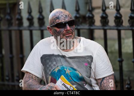 Un homme tatoué sur la rue, crâne rasé et avec des lunettes de soleil. Banque D'Images