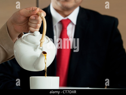 Woman pouring tea for businessman Banque D'Images