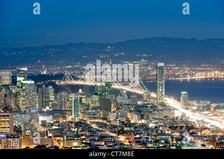 La tombée de la vue sur San Francisco et d'Oakland Bay Bridge depuis le sommet de Twin Peaks en Californie, USA. Banque D'Images