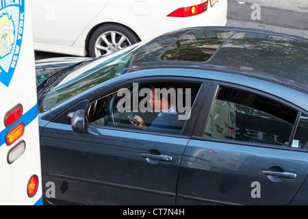 Dame femme pilote à l'aide de téléphone mobile tout en conduisant sa voiture dans la circulation dans la ville de Banque D'Images