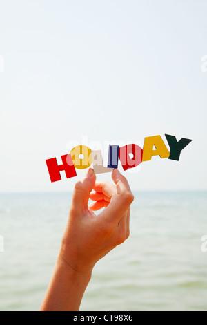 Femme's hand holding colorful mot 'vacances' contre la mer à la lumière du jour Banque D'Images