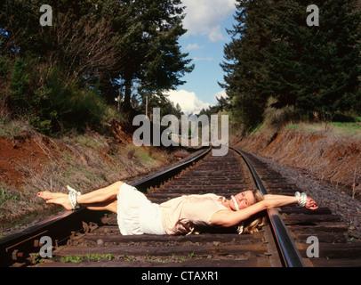 """Une femme attachée sur certaines voies de chemin de fer comme un 'damsel en détresse."""" Banque D'Images"""