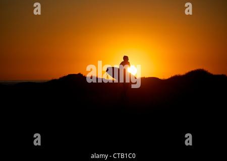 Surfer marcher le long de la plage pendant le coucher du soleil, Los Angeles, Californie, USA Banque D'Images