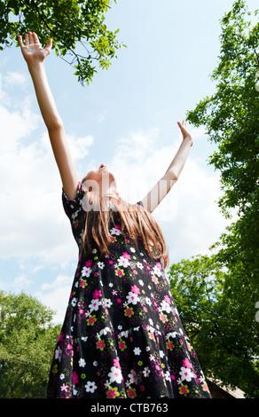 Fille de l'adolescence avec les mains posées contre blue cloudy sky Banque D'Images