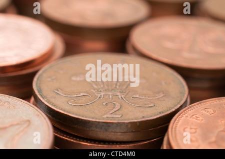 Deux pièces de cuivre pence dans une pile de pièces, UK £ Sterling Banque D'Images