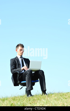 Business man with laptop on chair Banque D'Images