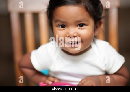 Heureux bébé fille tenant une cuillère et assis sur un siège d'appoint Banque D'Images