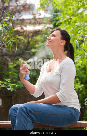 Femme de pulvériser sur le visage de brume dans jardin