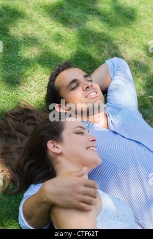 Heureux beau jeune homme et de la femme dans l'amour, allongé sur l'herbe en parc et relaxant Banque D'Images