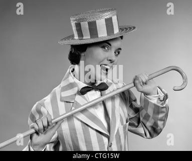 Années 50 costume de vaudeville femme dansant en costume rayé et chapeau avec CANNE À SUCRE Banque D'Images