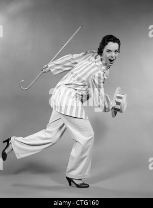 1950 FEMME EN blouson rayé HOLDING & canne de brassage des chapeau de paille de l'AVANT DANS LE DOMAINE DE LA DANSE Banque D'Images