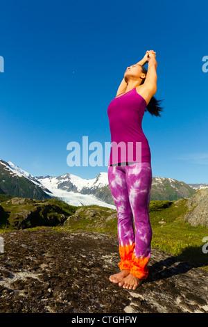 Korean woman stretching avec montagnes en arrière-plan Banque D'Images
