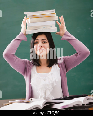 Caucasian student balancing books on head Banque D'Images