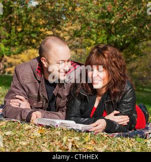 Couple lire la Bible ensemble dans un parc; Edmonton, Alberta, Canada Banque D'Images