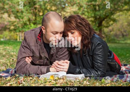 Couple Reading Bible et prier ensemble dans un parc; Edmonton, Alberta, Canada Banque D'Images