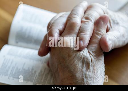 Du vieil homme altéré les mains jointes en prière sur Bible ouverte