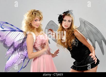 Deux jeunes femmes vêtues comme le bien et le mal faeries avec des ailes Banque D'Images