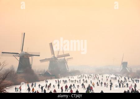 Patineurs néerlandais en face de cinq des 19 moulins à Kinderdijk dans l'Alblasserwaard polder, Hollande, Pays-Bas. Banque D'Images