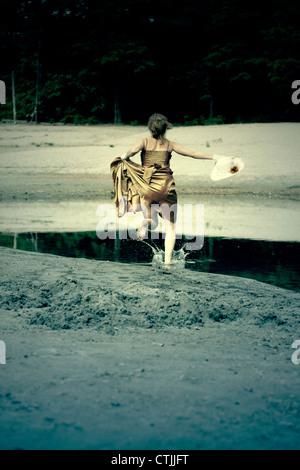 Une femme est en marche dans l'eau dans une robe Banque D'Images