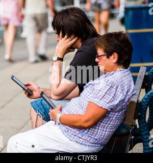 Un homme femme couple lecture des e-books sur leurs lecteurs Amazon Kindle, assis dehors sur une journée chaude, Banque D'Images
