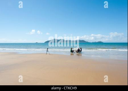 Wongaling beach de Mission Beach sur la côte casoar avec Dunk Island en vue et trois garçons en profitant de la Banque D'Images