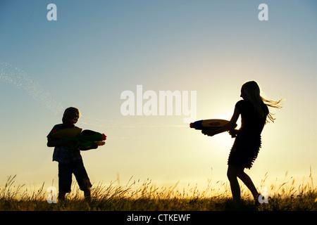 Garçon et fille se tirer dessus avec des pistolets à eau au coucher du soleil. Silhouette. UK Banque D'Images