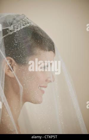 Une jeune mariée de porter un voile et diadème smiling, side view Banque D'Images