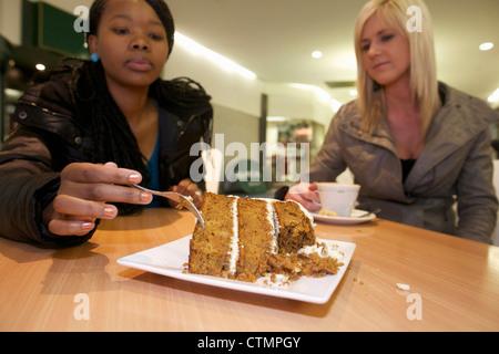 Deux jeunes femmes au café manger un gâteau et de boire du café, Pietermaritzburg, KwaZulu-Natal, Afrique du Sud Banque D'Images