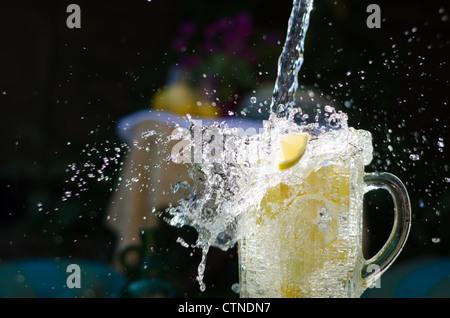 Verser de l'eau et en splahing verseuse en verre rempli de citrons sur la journée ensoleillée.
