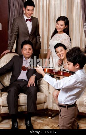 Petit garçon à jouer du violon à l'avant des membres de la famille