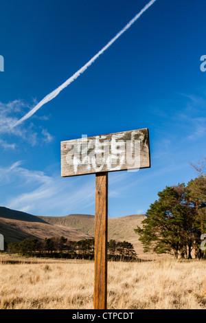 Un signe peint à la main sur un bâton en bois avise les personnes de boue profonde à un lac d'un parc national au Banque D'Images