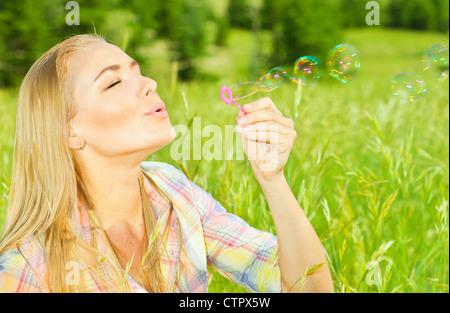 Jolie femme soufflant des bulles de savon en parc, sain bel femme jouant sur l'herbe verte, modèle sans souci de Banque D'Images