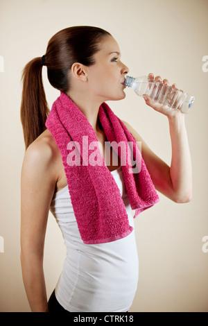 Une jeune femme portant des vêtements fitness, une bouteille d'eau potable Banque D'Images