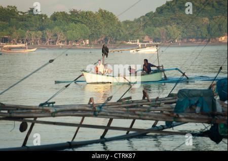 Les pêcheurs balinais retour au village d'Pemeuteran pour décharger leurs prises de la journée dans un outrigger Banque D'Images