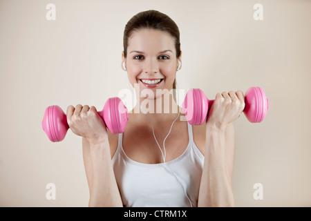 Une jeune femme l'entraînement avec haltères courtes rose, souriant à l'appareil photo Banque D'Images