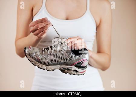 Une jeune femme défaisant les lacets d'une chaussure Banque D'Images