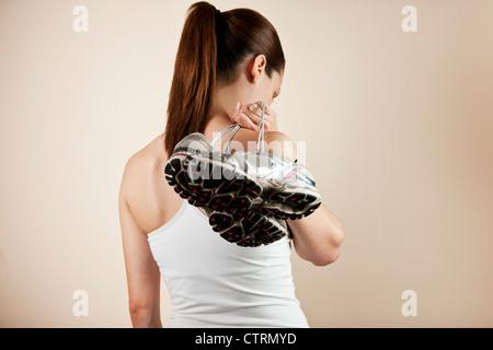 Une jeune femme portant une paire de chaussures de formation par-dessus son épaule, regardant vers le bas Banque D'Images