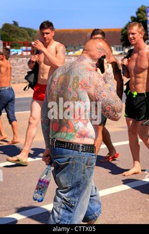 Fortement tattooed man expose ses œuvres corporelles au cours d'une journée d'été chaude Banque D'Images