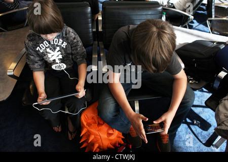 Deux garçons en attente dans un aéroport à l'aide d'appareils électroniques, un ipad et un ipod à jouer à des jeux Banque D'Images