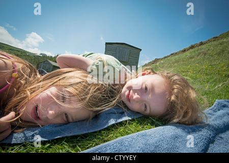Les jeunes filles portant sur des serviettes dans l'herbe Banque D'Images