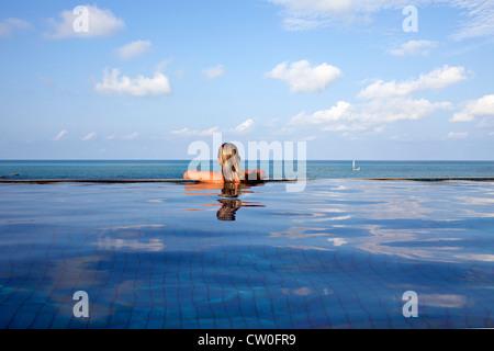Woman relaxing in piscine à débordement Banque D'Images