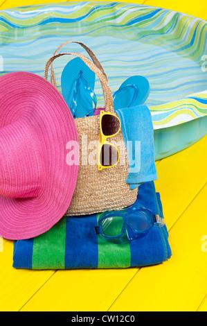 Un sac de plage de paille plein d'accessoires repose sur une serviette de plage à côté d'une piscine en plastique Banque D'Images